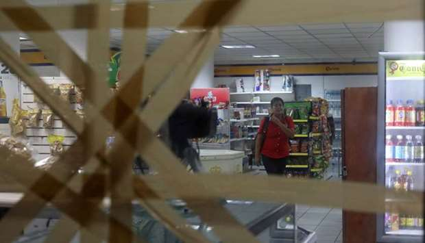 A woman is pictured inside a store with taped-up glass panels to protect against the expected severe