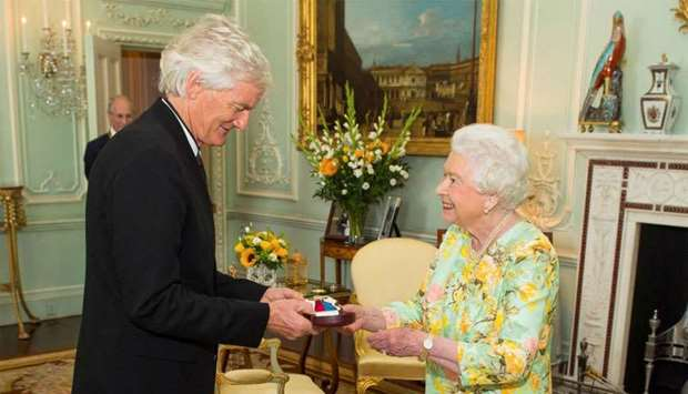 Britain's Queen Elizabeth presents James Dyson with the insignia of members of the Order of Merit