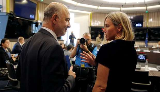 European Economic Commissioner Moscovici talks with EU Foreign Policy Chief Mogherini as they arrive