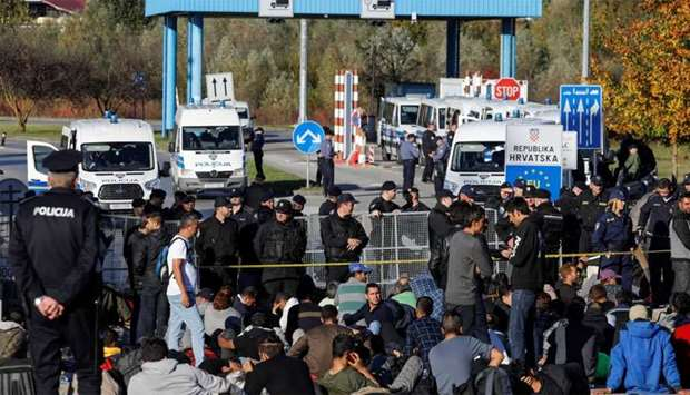 Bosnian and Croatian border police stand guard in front of migrants at Maljevac border crossing betw