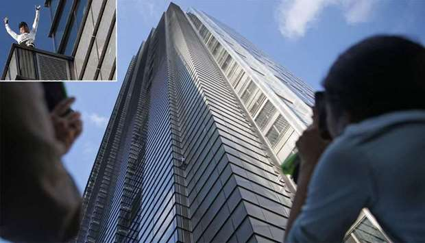 """People look up as French urban climber Alain Robert, also known as """"Spider-Man"""", climbs Heron Tower"""
