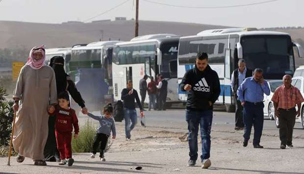 People walk as they wait to travel to Syria at Jordan's Jaber border crossing, near Syria's Nassib c