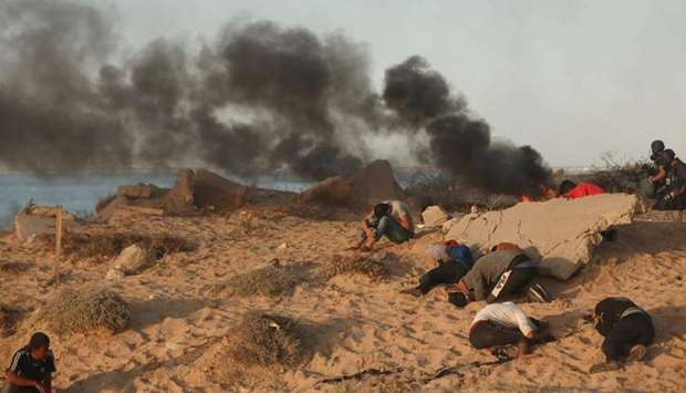 Palestinian protesters burn tyres during a demonstration on the beach near the maritime border with