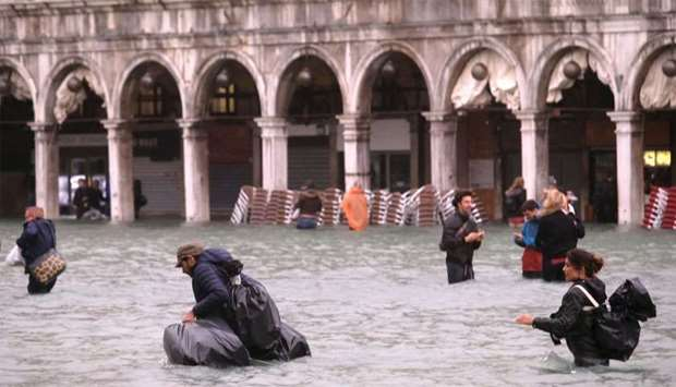 People walk in a flooded Saint Mark Square in Venice