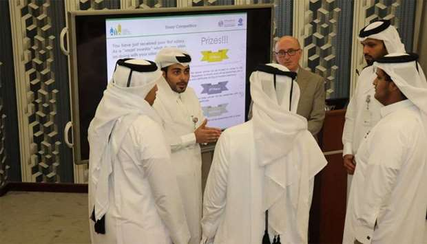 Regulatory Authority employees Abdulrahman al-Hail and John Pyne, second and fourth from the left, d