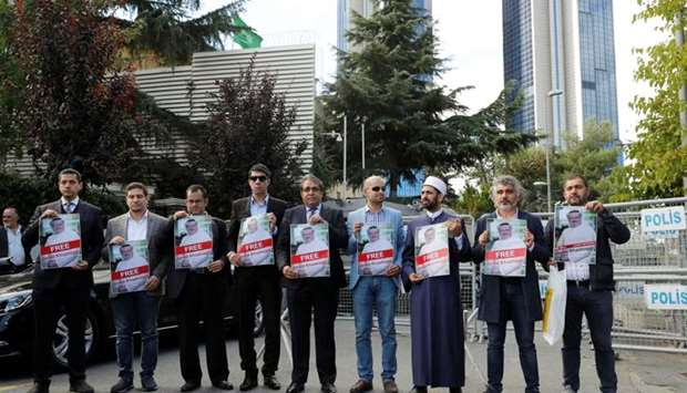 Demonstrators hold pictures of Saudi journalist Jamal Khashoggi during a protest in front of Saudi A