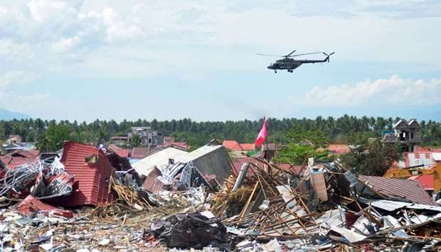 A military helicopter flies past a devastated area in Palu