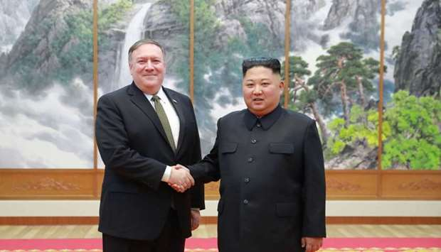 North Korea's leader Kim Jong Un (R) shaking hands with US Secretary of State Mike Pompeo
