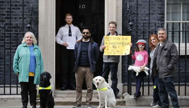 Campaigners with guide dogs pose outside number 10, Downing Street as they drop off a petition follo