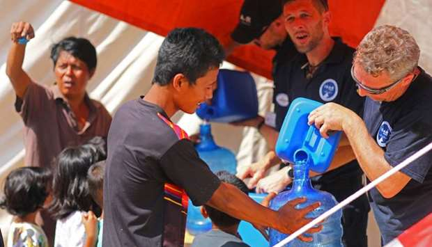 Members of Germany's NGO organisation ISAR-Germany (International Search and Rescue) give purified w