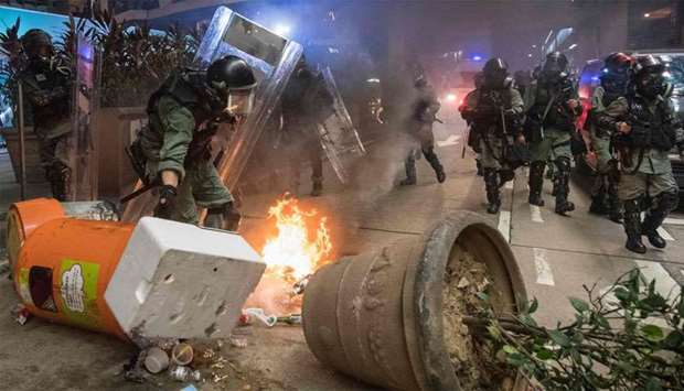 Police pass a burning roadblock in the Causeway Bay area of Hong Kong