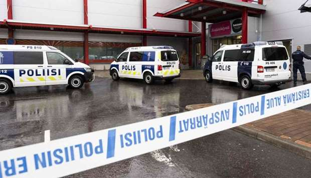 Police cars stand on the blocked grounds of the Hermanni shopping centre in Kuopio, Finland, after a