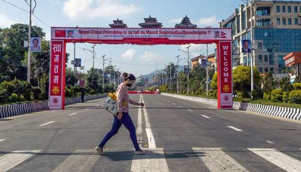 A woman crosses a road in front of a banner welcoming China's president Xi Jinping ahead of his stat