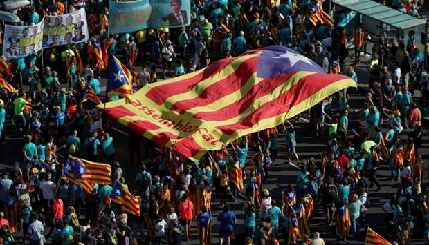 """People hold a giant """"Estelada"""" (Catalan separatist flag) at a rally during Catalonia's national day"""