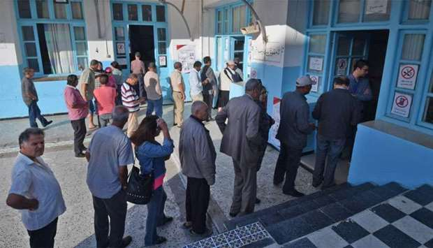 Tunisian voters queue outside a polling station in the capital Tunis during the second round of the