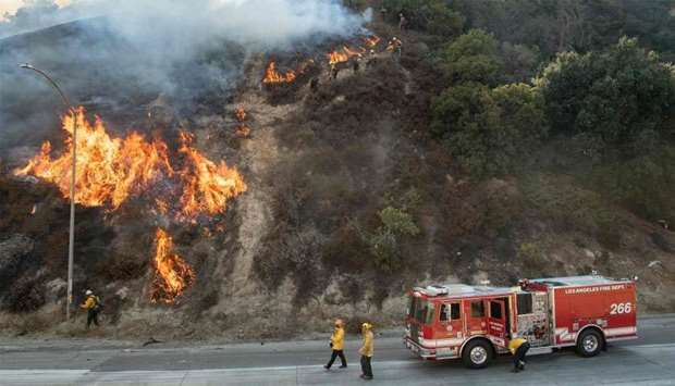 Firefighters check on a backfire during the Saddleridge fire in Newhall, California