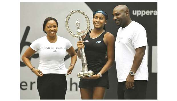 Coco Gauff of the US (centre) poses with the trophy next to her parents Gorey (right) and Candy Gauf