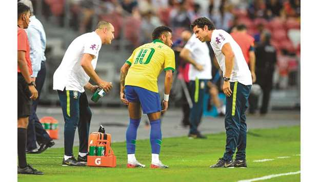 Brazil's forward Neymar (left) leaves the field after suffering an injury during an international fr