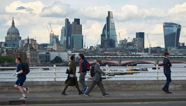 The skyline of buildings in The City of London is seen from Waterloo Bridge as pedestrians walk by i