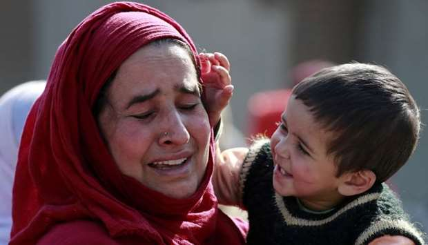 A Kashmir woman mourns as she carries a child during the funeral procession of Nasir Ahmad, a suspec