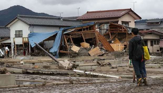 A man looks at flood-damaged homes in Nagano after Typhoon Hagibis hit Japan