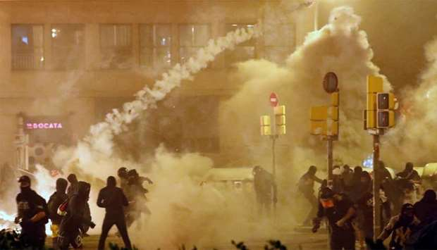 Catalan demonstrators throw back to the police a tear gas canister officer during Catalonia's genera