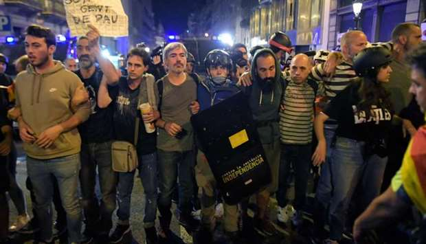 Protesters make a cordon between police and a sit-in following a demonstration called the Catalan pr