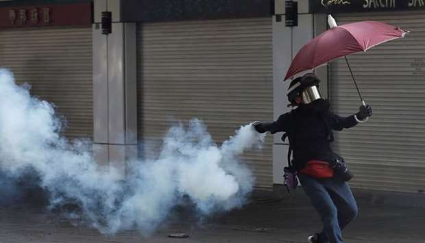 An anti-government demonstrator throws back a tear gas canister during a protest in Hong Kong
