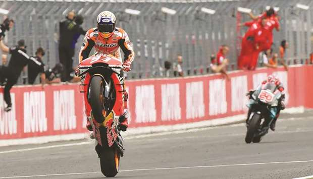 Repsol Honda's Marc Marquez pops a wheelie while crossing the finish line to win the Japanese MotoGP