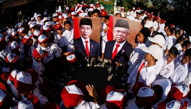 Students hold the pictures of Indonesian President Joko Widodo and Vice President Ma'ruf Amin during