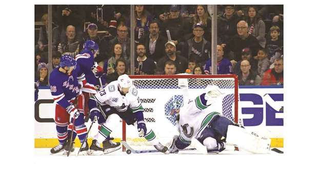 Vancouver Canucks' Jacob Markstrom (right) makes a save during the NHL game against the New York Ran