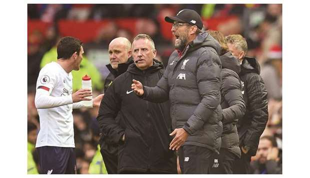 Liverpool's German manager Jurgen Klopp reacts as fourth official Jonathan Moss (C) looks on during