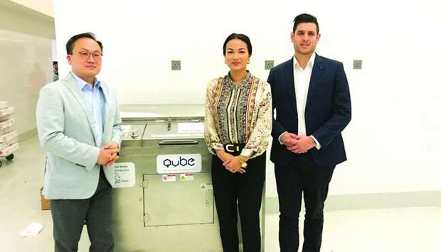 Qatar Upcycling & Biodegradables Enterprise (QUBE) officials with one of the machines that convert f