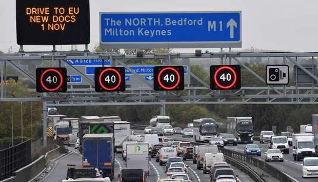 Traffic is seen passing government Brexit information campaign signs on the M1 motorway near Milton