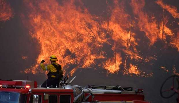Firefighters battle a wind driven wildfire in the hills of Canyon Country north of Los Angeles, Cali