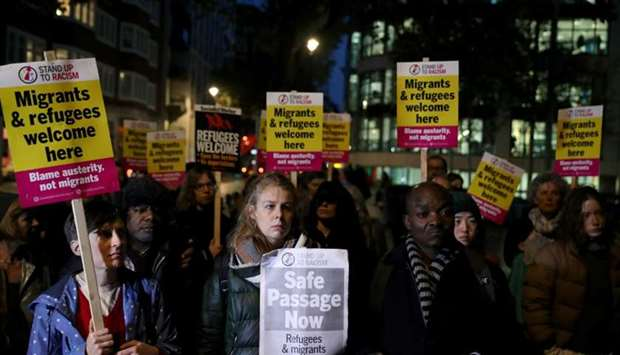 Anti-racism campaigners take part in a vigil, following the discovery of 39 bodies in a truck contai