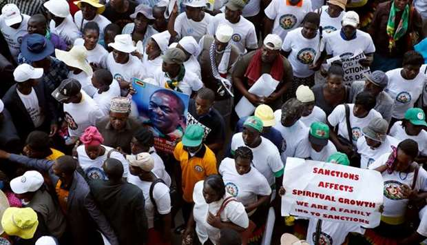 Government supporters chant slogans as they march against Western sanctions at a rally in Harare, Zi