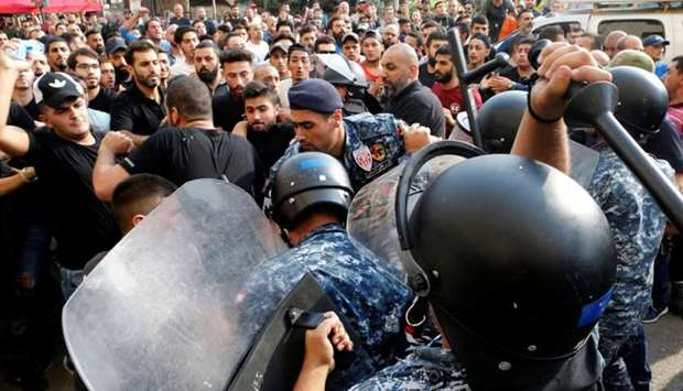 Riot police officers scuffle with Hezbollah supporters during ongoing anti-government protests in do