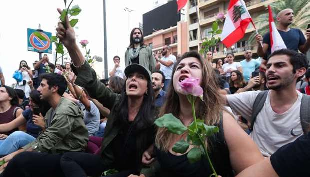 Lebanese actress and film director Nadine Labaki (C) holds a rose as she takes part with fellow demo