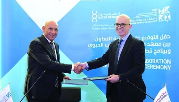 Dr Omar El Agnaf, executive director of QBRI, and Dr Said Ismail, Qatar Genome director, shake hands