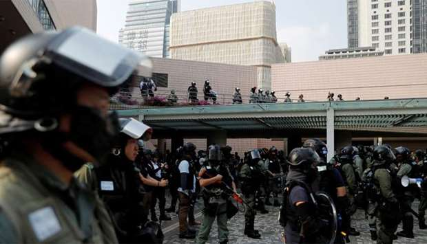Police officers stand guard during an anti-government protest in Hong Kong's tourism district of Tsi
