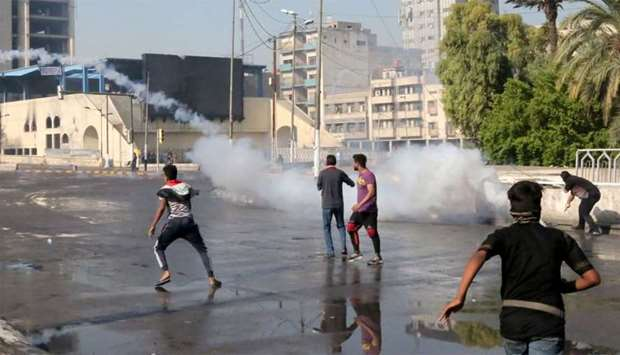 Demonstrators gather in the Iraqi capital Baghdad's Tahrir square as security forces use tear gas to