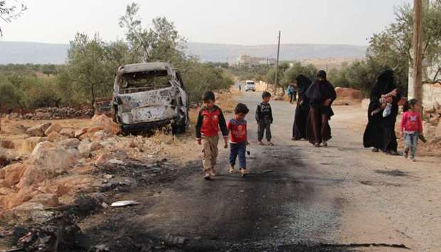 Syrians walk past a damaged van at the site of helicopter gunfire which reportedly killed nine peopl