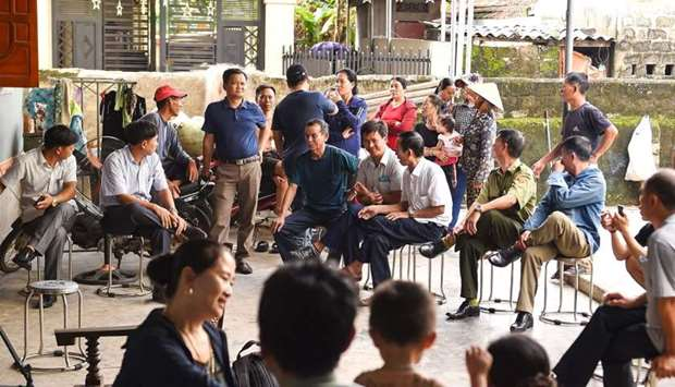 Villagers and local police personnel gather at the house of 18-year old Hoang Van Tiep who is feared