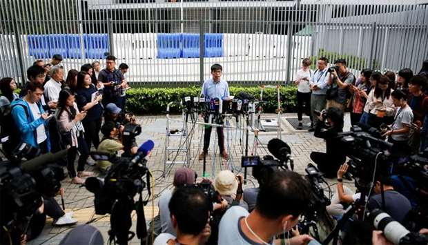 Pro-democracy activist Joshua Wong speaks to journalists after being disqualified from running in lo
