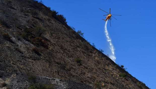 A helicopter makes a water drop over hillsides near in Los Angeles