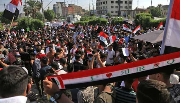 Iraqis take part in ongoing anti-government protests in the central city of Karabala