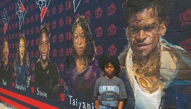Lauryn Renford poses in front of a mural by Martin Swift depicting teenage gun violence victims in W
