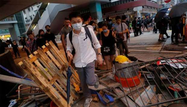 People walk over a barricade in Hong Kong, China