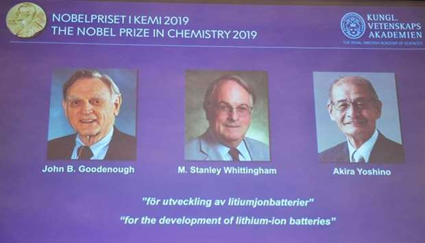 A screen displays the portraits of the laureates of the 2019 Nobel Prize in Chemistry (L-R) John B.